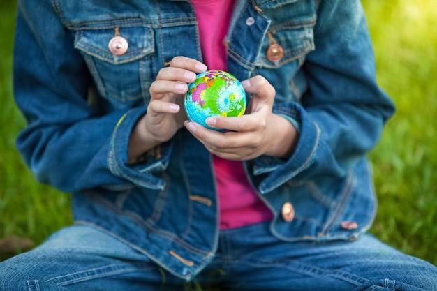 Nahaufnahmefoto des kleinen mädchens, das globus hält und es erforscht