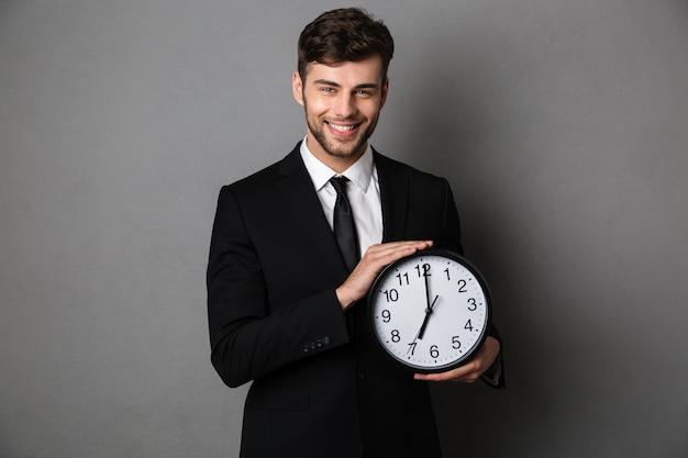 Nahaufnahmefoto des lächelnden gutaussehenden mannes im schwarzen anzug, der uhr hält,