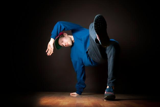 Nahaufnahmefoto des männlichen breakdancer, der haltung vor dunklem hintergrund durchführt b