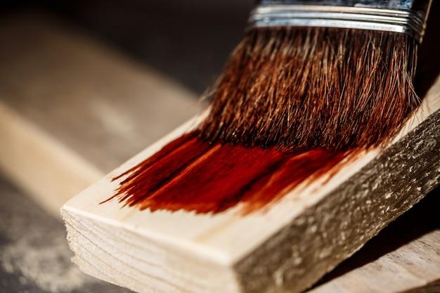 Nahaufnahmefoto des malens des holzes in der braunen farbe.