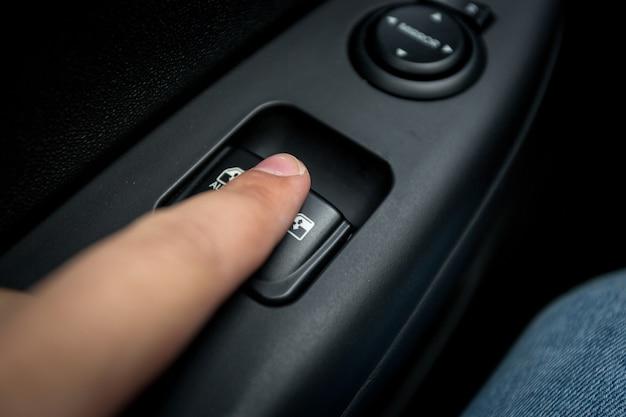 Nahaufnahmefoto des mannes, der die taste zur steuerung des fensters im auto drückt