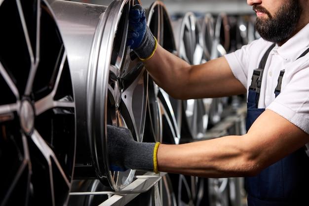 Nahaufnahmefoto des mannes in den handschuhen, die automatische felgen vom gestell nehmen, abgeschnittener automechaniker in der uniform bei der arbeit
