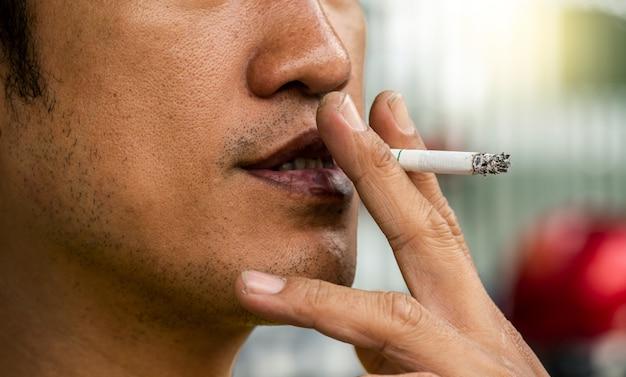 Nahaufnahmefoto des rauchenden mannes mit schmutzigem