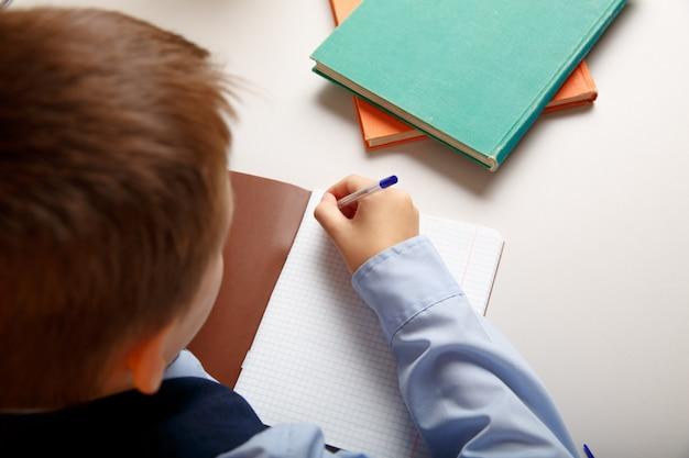 Nahaufnahmefoto des schülers, der im notizbuch an der lektion schreibt.