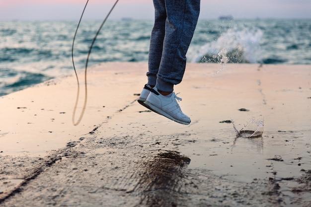 Nahaufnahmefoto des springenden mannes in der sportkleidung mit springseil, praxis auf pier