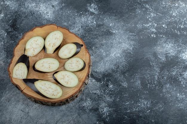Nahaufnahmefoto des stapels der geschnittenen aubergine auf holzbrett.
