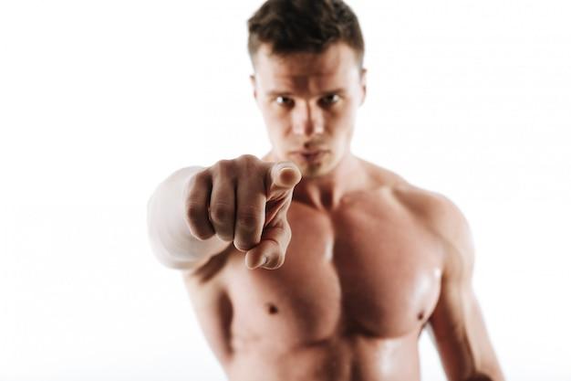 Nahaufnahmefoto des starken sportmannes mit dem kurzen haarschnitt, der mit finger auf sie zeigt, selektiver fokus auf finger