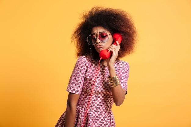Nahaufnahmefoto des verärgerten retro-mädchens mit afro-frisur, die mit retro-telefon aufwirft