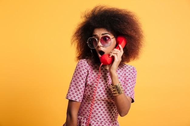 Nahaufnahmefoto des verblüfften retro-mädchens mit afro-frisur, die retro-telefon hält
