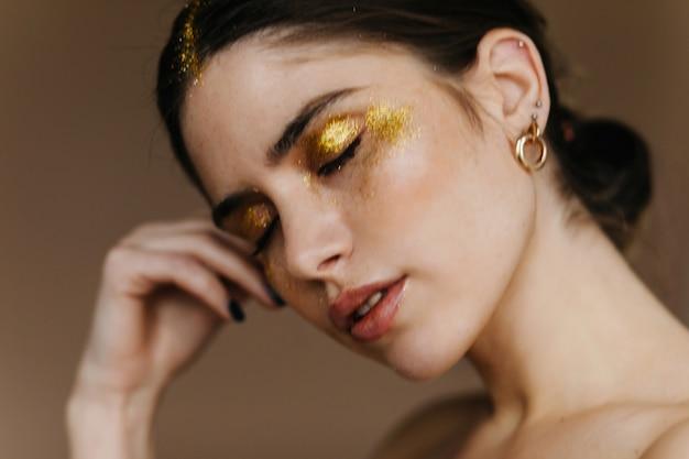 Nahaufnahmefoto des verschlafenen mädchens mit party make-up. innenporträt der hübschen schwarzhaarigen frau, die auf dunkler wand aufwirft.