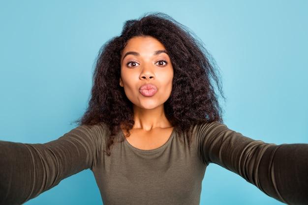 Nahaufnahmefoto des verträumten romantischen gefühls romantik schwarzes hautmädchen im urlaub nehmen selfie videoanruf senden luftküsse tragen stilvolles hemd isoliert über blaue farbe wand