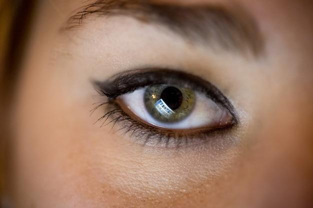 Nahaufnahmefoto des weiblichen auges mit computerbildschirm, der sich darin widerspiegelt