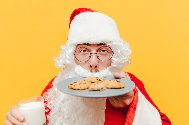 Nahaufnahmefoto des weihnachtsmannes, der die leckeren schokoladenplätzchen riecht