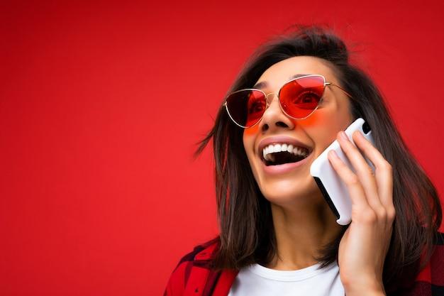 Nahaufnahmefoto einer attraktiven, glücklichen, positiven jungen brunet-frau, die ein stylisches rotes hemd, ein weißes t-shirt und eine rote sonnenbrille trägt, isoliert auf rotem hintergrund, die auf dem handy nach oben kommuniziert