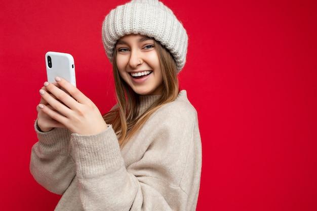 Nahaufnahmefoto einer attraktiven lächelnden, positiv aussehenden jungen frau, die lässig stylisch trägt wearing