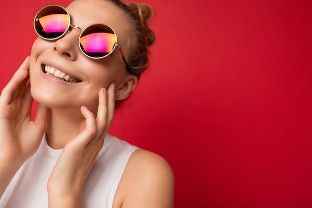 Nahaufnahmefoto einer attraktiven, sexy, fröhlichen jungen blonden frau, die alltägliche stilvolle kleidung und eine moderne sonnenbrille trägt, die auf einer bunten hintergrundwand mit blick auf die kamera isoliert ist