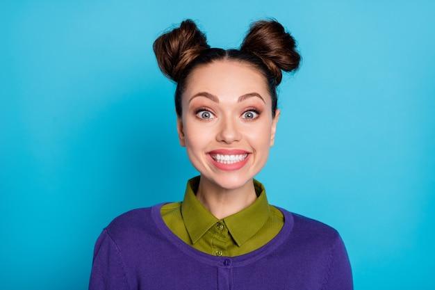 Nahaufnahmefoto einer attraktiven verrückten dame, zwei lustige brötchen, die weiße zähne zeigen, breites lächeln, studenten medizinische untersuchung tragen hemdkragen violetter pullover isoliert blauer farbhintergrund