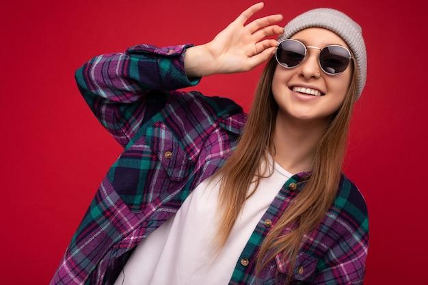 Nahaufnahmefoto einer bezaubernden lächelnden jungen blonden frau, die über rotem hintergrund isoliert ist und bunte trägt
