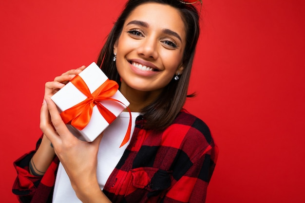 Nahaufnahmefoto einer charmanten, glücklich lächelnden jungen brunet-frau, die auf roter hintergrundwand isoliert ist?