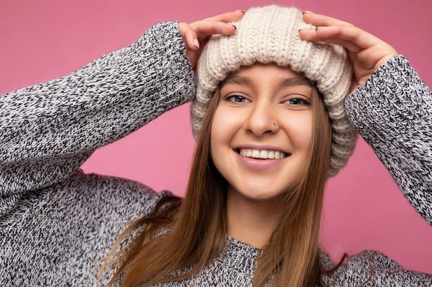 Nahaufnahmefoto einer charmanten, positiv glücklich lächelnden jungen dunkelblonden frau, die über einer bunten hintergrundwand isoliert ist und die alltägliche modische kleidung trägt und in die kamera schaut.