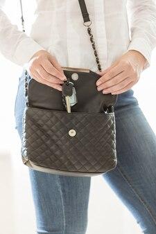 Nahaufnahmefoto einer frau, die hausschlüssel aus der handtasche nimmt