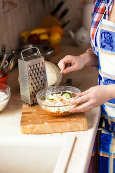 Nahaufnahmefoto einer frau, die salat mit gabel in der küche isst