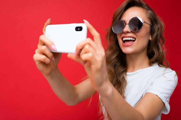 Nahaufnahmefoto einer glücklichen jungen blonden frau, die ein handy hält und ein selfie-foto mit dem smartphone macht