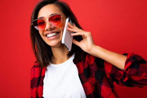 Nahaufnahmefoto einer hübschen, glücklich lächelnden jungen brunet-frau, die ein stylisches rotes hemd, weißes t-shirt und eine rote sonnenbrille trägt, isoliert auf rotem hintergrund, die auf dem handy mit blick auf die kamera kommuniziert