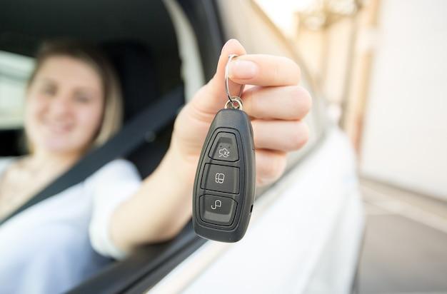 Nahaufnahmefoto einer lächelnden frau, die ein auto mit autoschlüsseln fährt