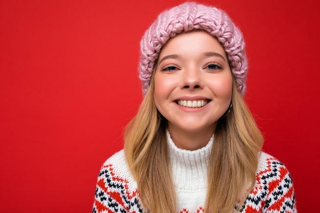 Nahaufnahmefoto einer schönen, glücklich lächelnden jungen blonden frau, die isoliert über einer bunten hintergrundwand steht und alltägliche modische kleidung trägt und in die kamera schaut, die gesichtsgefühle zeigt.