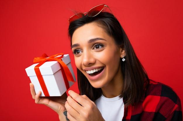 Nahaufnahmefoto einer schönen glücklich lächelnden jungen brunet-frau, die auf roter hintergrundwand isoliert ist und ein weißes, lässiges t-shirt und ein stilvolles rotes und schwarzes hemd trägt, das eine weiße geschenkbox mit rotem band und look hält