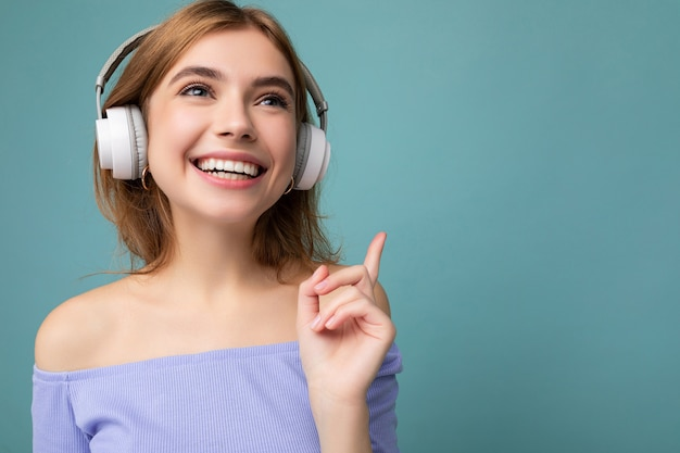 Nahaufnahmefoto einer schönen, positiv lächelnden jungen blonden frau mit blauem bauchfreiem oberteil isoliert über