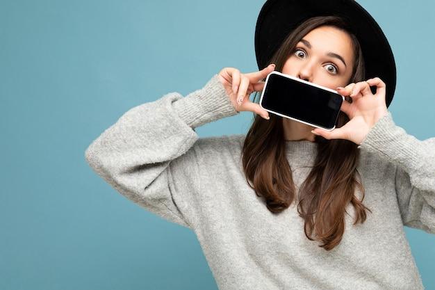 Nahaufnahmefoto einer schönen positiven frau mit schwarzem hut und grauem pullover, die ein mobiltelefon hält und das smartphone einzeln auf dem hintergrund mit blick auf die kamera zeigt