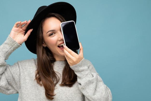Nahaufnahmefoto einer schönen positiven frau mit schwarzem hut und grauem pullover