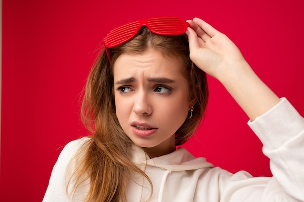 Nahaufnahmefoto einer schönen traurigen jungen blonden frau, die freizeitkleidung und stilvolle optik trägt