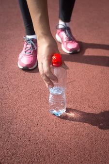 Nahaufnahmefoto einer sportlichen frau, die eine flasche wasser von der laufstrecke nimmt