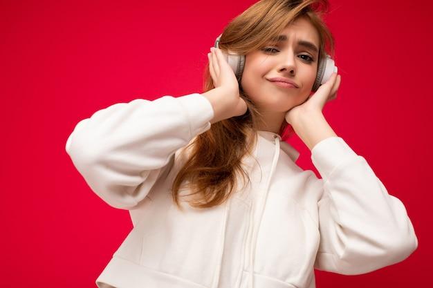 Nahaufnahmefoto einer ziemlich positiv lächelnden jungen blonden frau, die einen weißen hoodie trägt, isoliert über