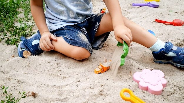 Nahaufnahmefoto eines 3 jahre alten kleinkindjungen, der mit spielzeug im sandkasten auf dem spielplatz spielt