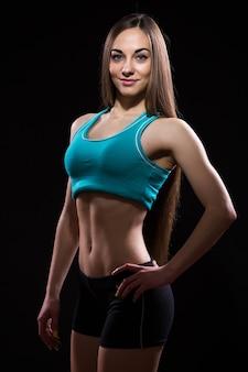 Nahaufnahmefoto eines fitnessmodellkörpers auf schwarzem hintergrund