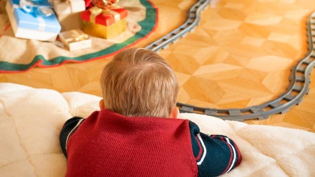 Nahaufnahmefoto eines kleinen jungen, der auf dem boden liegt und seine spielzeugeisenbahn im wohnzimmer auf eisenbahnen betrachtet