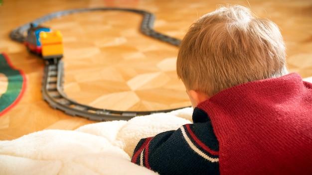 Nahaufnahmefoto eines kleinen jungen, der seine spielzeugeisenbahn auf eisenbahnen auf holzboden im haus beobachtet