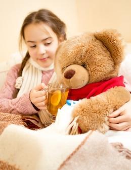 Nahaufnahmefoto eines kranken mädchens, das im bett liegt und dem teddybären tee gibt