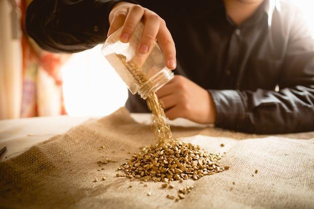 Nahaufnahmefoto eines männlichen bergmanns, der ein glas mit goldenen nuggets leert