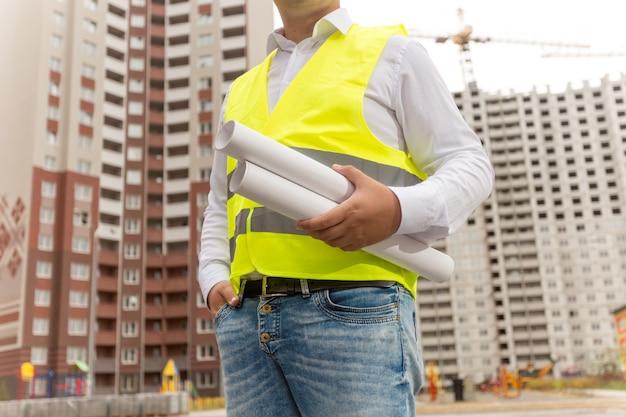 Nahaufnahmefoto eines männlichen ingenieurs, der blaupausen und dokumente hält