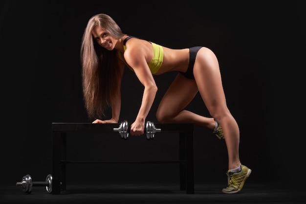Nahaufnahmefoto eines sportfrauenporträts, das schwarze sportbekleidung mit hanteln trägt, die muskelbizeps über dunkelheit aufpumpen