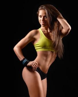 Nahaufnahmefoto eines sportfrauenporträts, das schwarze sportbekleidung über dunkelheit trägt