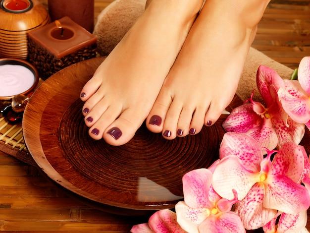 Nahaufnahmefoto eines weiblichen fußes am spa-salon auf pediküreverfahren. beinpflegekonzept