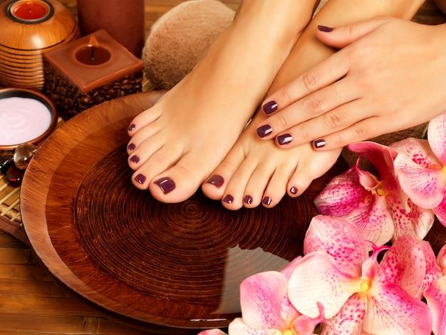 Nahaufnahmefoto eines weiblichen fußes am spa-salon auf pediküreverfahren. weibliche beine in wasserdekoration die blumen.