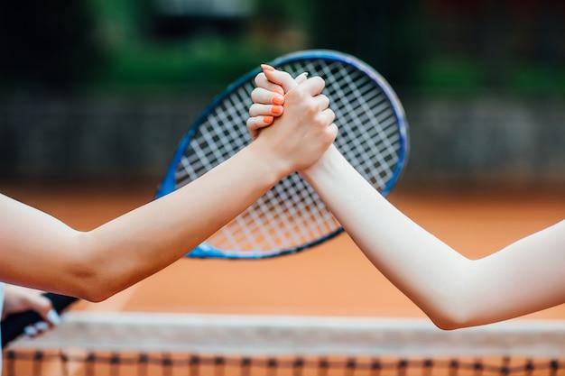 Nahaufnahmefoto. junge mädchen, die hände auf dem tennisplatz, lächelnd rütteln.