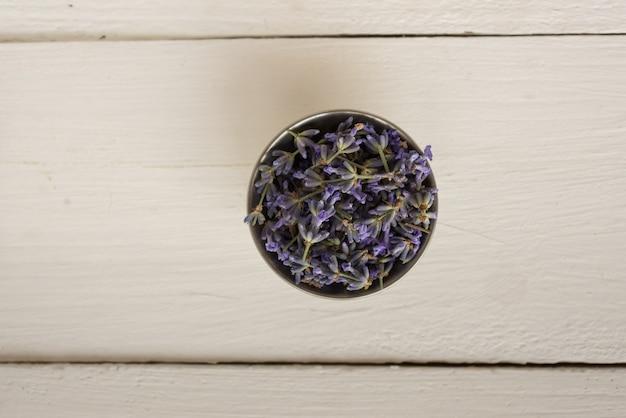 Nahaufnahmefoto oben auf einem holz mit einer kleinen schüssel mit duftendem lavendel. draufsicht